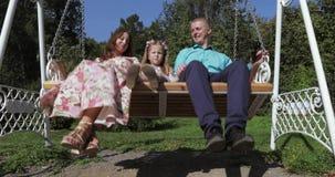 Mädchenkind auf einem Schwingen mit ihren Eltern stock footage