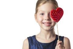 Mädchenkind, das einen Herz-förmigen Lutscher hält Getrennt Stockbild