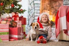 Mädchenkind, das zu Hause ein glückliches Weihnachten durch das fireplac feiert stockfoto