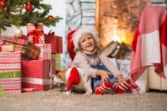 Mädchenkind, das zu Hause ein glückliches Weihnachten durch das fireplac feiert stockfotos