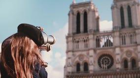 Mädchenkind im Barett schaut durch Münzenferngläser Langsame Bewegung Notre-Dame de Paris Münzenteleskop tourismus stock footage