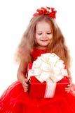 Mädchenkind im roten Kleid mit Geschenkkasten. Stockfoto