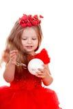 Mädchenkind im roten Kleid mit Weihnachtskugel. Lizenzfreie Stockbilder