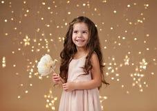 Mädchenkind ist in den Weihnachtslichtern, gelber Hintergrund, rosa Kleid stockfotos