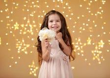 Mädchenkind ist in den Weihnachtslichtern, gelber Hintergrund, rosa Kleid lizenzfreie stockfotografie