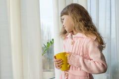 Mädchenkind 7 Jahre alte Blondine mit dem langen gewellten Haar in einer warmen gestrickten Strickjacke hält eine Tasse Tee und s lizenzfreie stockfotografie