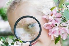 Mädchenkind mit einer Lupe in den Blumen, Frühling Lizenzfreie Stockbilder