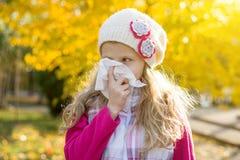 Mädchenkind mit kalter Rhinitis auf Herbsthintergrund stockfoto