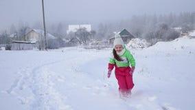 Mädchenkinderläufe auf schneebedeckter Straße Aktive Feiertage für bewölkten Wintertag der Kind A stock video
