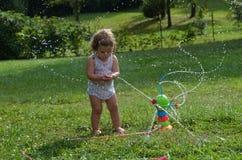 Mädchenkleinkind, das mit einer Spielzeugberieselungsanlage spielt Lizenzfreies Stockfoto