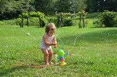 Mädchenkleinkind, das mit einer Spielzeugberieselungsanlage spielt Lizenzfreie Stockbilder