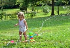 Mädchenkleinkind, das mit einer Spielzeugberieselungsanlage spielt Lizenzfreie Stockfotos