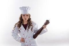 Mädchenkoch mit Pfeffer stockfoto