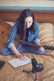 Mädchenkomponist schreibt, in verfassende Musik des Notizbuches auf Gitarre und in blogging auf Kamera Lizenzfreie Stockfotos