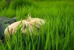 Mädchenkopf im Gras Stockbilder