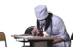 Mädchenkrankenschwester überprüft Blutuntersuchung unter Verwendung eines Mikroskops Stockfotografie