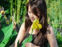 Mädchenlächeln und -blick in Blume Stockfotos