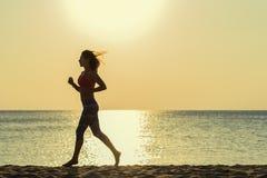 Mädchenläufe entlang dem Strand Stockfoto