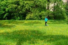 Mädchenläufe entlang der Spur, sonniger Tag des Sommers stockfotografie