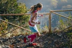 Mädchenläufer läuft auf einem Gebirgspfad im Hintergrund des Gebirgstales Stockfotografie