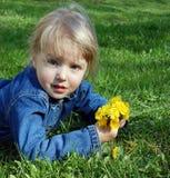 Mädchenlüge auf Gras mit Blumen Lizenzfreie Stockfotografie