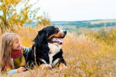 Mädchenlügen nahe bei großem Hund auf Herbst gehen stockbilder