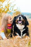 Mädchenlügen nahe bei großem Hund auf Herbst gehen stockfoto