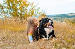 Mädchenlügen nahe bei großem Hund auf Herbst gehen stockfotos
