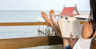 Mädchenlesebuch auf dem Balkon mit Küstenansicht stockfotografie