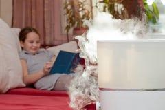 Mädchenlesebuch auf dem Hintergrund des Befeuchters Stockbilder