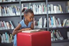 Mädchenlesebuch auf Osmanen in der Bibliothek lizenzfreie stockfotos