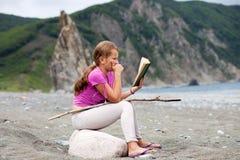 Mädchenlesebuch, das auf einem Stein auf einem sandigen Seeufer sitzt Lizenzfreie Stockfotos