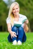 Mädchenlesebuch sitzt auf dem Gras lizenzfreies stockbild