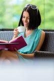 Mädchenlesebuch trinkt Tee am Café lizenzfreies stockbild