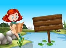 Mädchenlesekarte durch den Fluss Stockbilder