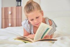 Mädchenlesung, die auf Bett liegt stockfotos