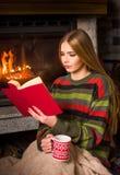 Mädchenlesung durch den Kamin, der auf dem Boden sitzt lizenzfreie stockbilder