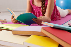 Mädchenlesung unter zerstreuten Büchern auf dem Boden Lizenzfreie Stockfotos