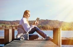 Mädchenlesung von einer Tablette Stockfotos