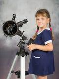 Mädchenliebhaber von Astronomie steht nahe bei dem Teleskop und den Rahmen untersucht stockfotografie