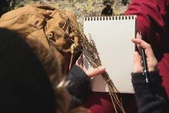 Mädchenmaler zeichnet einen Bleistift in einem Notizbuch auf Natur in den Bergen Freie Kreativität und Freiberuflich tätig sein stockfoto