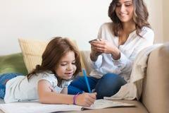 Mädchenmalerei mit ihrer chating Mutter Stockfotografie