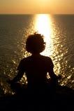 Mädchenmeditation auf dem Felsen über Meer Stockbild