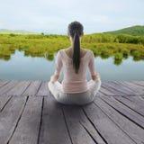 Mädchenmeditation im Holzfußboden stockbild