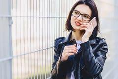 Mädchenmitteilung auf Telefon und dem Lächeln stockfotografie