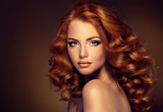Mädchenmodell mit dem langen gelockten roten Haar Stockfotografie