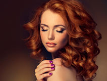 Mädchenmodell mit dem langen gelockten roten Haar Stockfoto