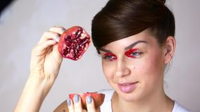 Mädchenmodell mit hellem Make-up Mädchen mit roter Frucht mit Granatäpfeln in den Händen stock video