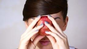 Mädchenmodell mit hellem Make-up Mädchen mit roter Frucht mit Granatäpfeln in den Händen stock footage