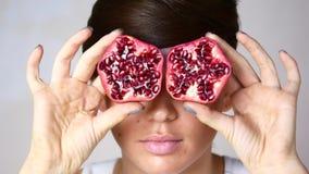 Mädchenmodell mit hellem Make-up Mädchen mit roter Frucht mit Granatäpfeln in den Händen stock video footage